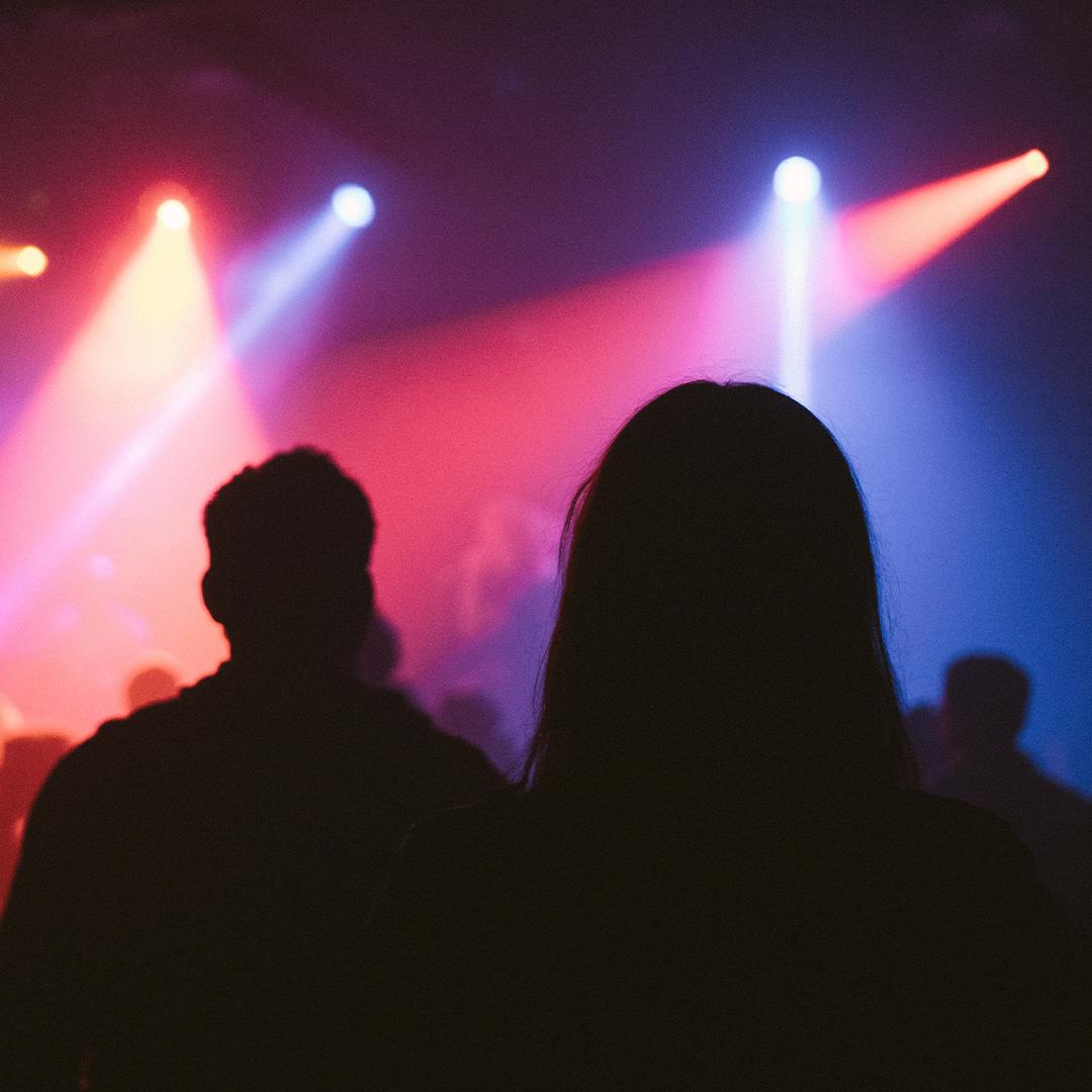 En mann og kvinne som står med ryggen til på en konsert